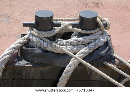 Old ropes around rusty mooring bollard in a dock - stock photo