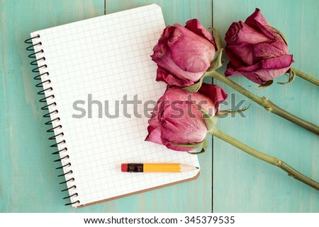 Old roses and blank notebook over wooden table. Top view with copy space.