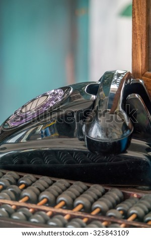 Old rotary phone, and wooden abacus on old table - stock photo