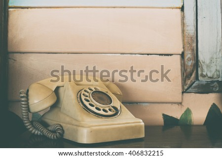 Old rotary telephone on wooden table with vintage filter background - stock photo