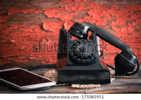 Old rotary telephone with its receiver off the hook alongside a tablet computer showing the old-fashioned and modern forms of communication against a grungy wooden wall with peeling paint - stock photo