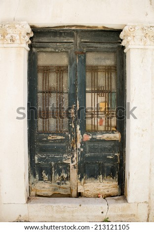 old rotting door in the old town - stock photo