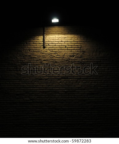 Old rough brick wall background texture with a spotlight shining on it - stock photo