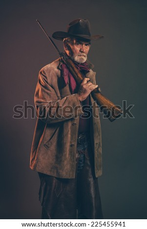 Old rough western cowboy with gray beard and brown hat holding rifle. Low key studio shot. - stock photo