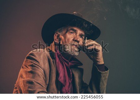 Old rough western cowboy with gray beard and brown hat smoking a cigarette. Low key studio shot. - stock photo