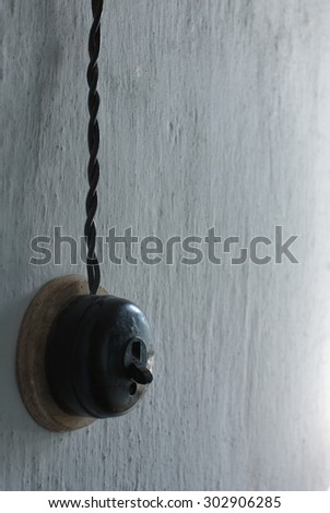 Old round black electricity switch on the white wall. Spiral cable goes from switch. Sidelight good shows texture of the wall. - stock photo