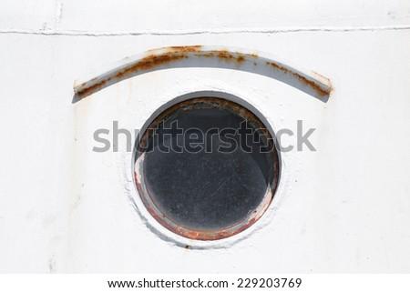 Old round rusted porthole on white ship hull - stock photo
