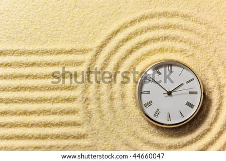Old round watch on a surface of golden sand - stock photo