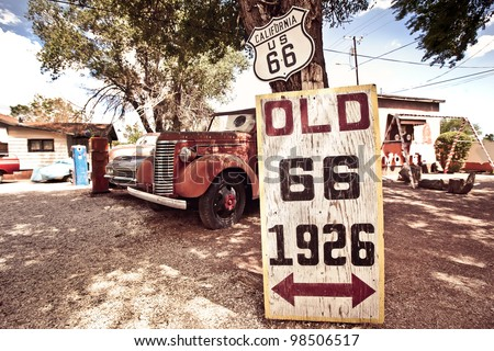 Old route 66 signs with rusty cars in background - stock photo