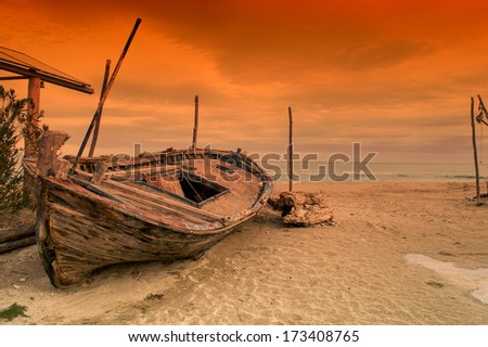 Old row boat on a beach at sunset - stock photo