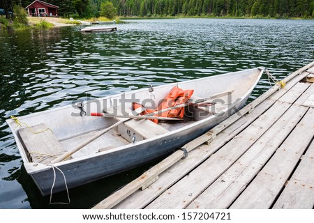 Old Row Boat with Life Jackets Moored to Dock in Lake - stock photo
