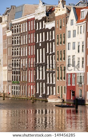Old row houses by the canal in the city of Amsterdam, Holland, Netherlands.