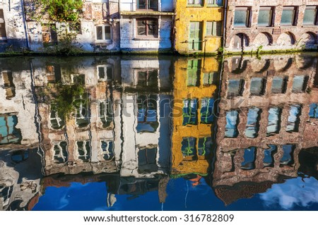 old row houses reflecting in the water of a canal in the old town of Ghent, Belgium - stock photo