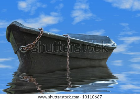 Old rowboat drifting on the water under a summer sky - stock photo