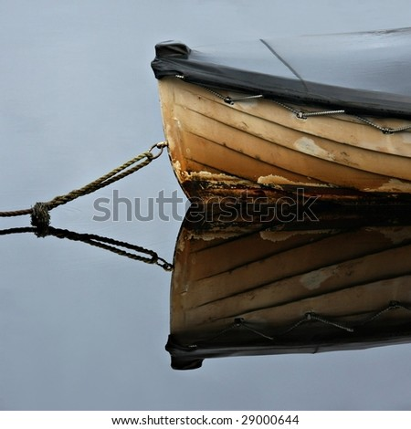 Old rowboat moored in a peacuful bay - Strahan, Tasmania - stock photo
