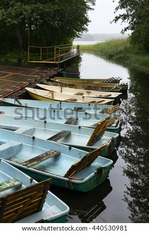 Old rowing boats on a wooden pier, a vertical picture