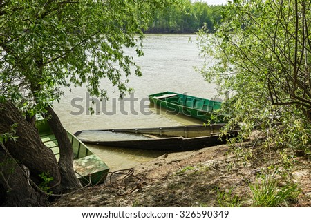 Old rowing fishing boats are tied and marooned with chains to the river shore. - stock photo