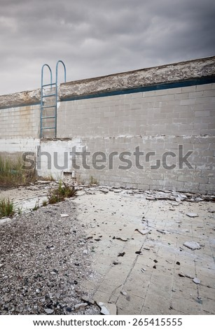 Old ruined abandoned swimming pool with ladder  - stock photo