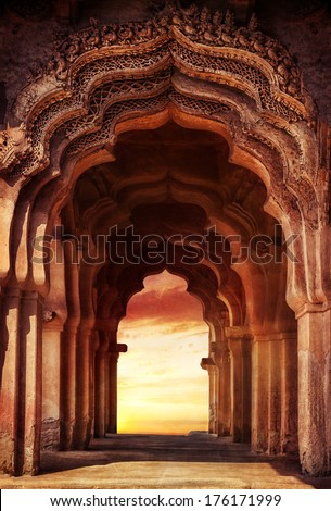 Old ruined arch in ancient temple at sunset in India - stock photo