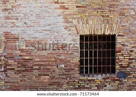 Old Ruined Brick Wall With Square Window - stock photo