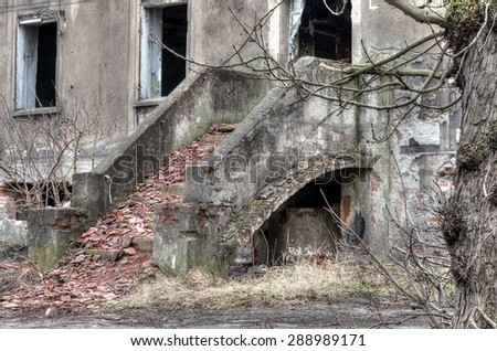 Old ruined building. exterior stairs lead into left collapsing house, the object falling into ruin is probably inhabited by homeless people.