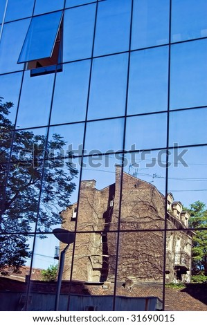 Old ruined building reflecting in windows of modern business building - stock photo