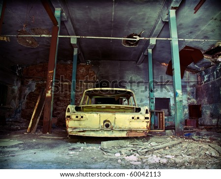 old ruined garage interior with old car - stock photo