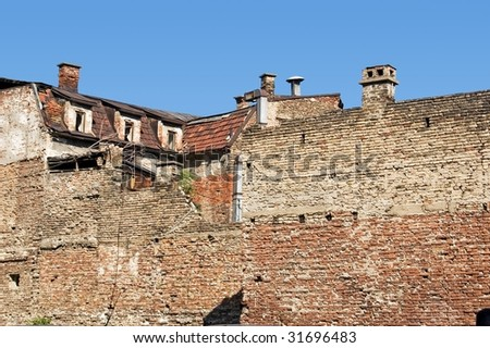 Old ruined house in down town of big city - stock photo
