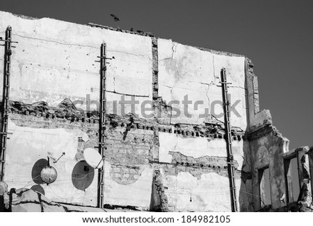Old ruined house with two rusty satellite dishes and birds (pigeons) sitting over the wall. Nobody.  Life is going on idea. Aged photo. Black and white. - stock photo