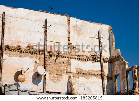 Old ruined house with two rusty satellite dishes and birds (pigeons) sitting over the wall. Nobody. Life is going on idea. - stock photo