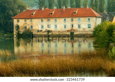 Old ruined rusty castle on the Mreznica river in Duga Resa, Croatia, reflection on water - stock photo