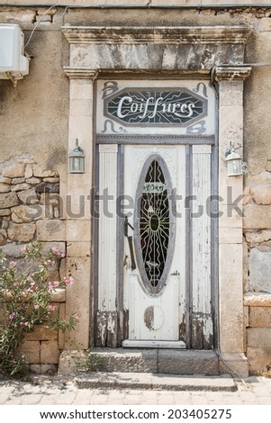 Old ruined wooden door of a destroyed house with the name coiffeur. - stock photo