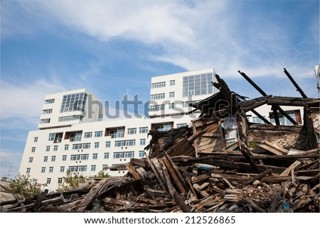 old ruined wooden house on the background of the new buildings - stock photo