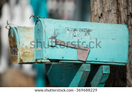 old rural blue mailboxes against a tree with a picket fence in background - stock photo