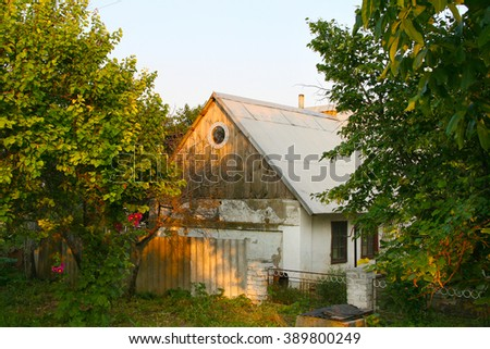 old rural ukrainian vintage wooden home house farm building cottage village, on sunset orange light near the green grass and trees, Odessa, Ukraine - stock photo