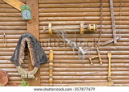Old rural utensils hang on log wall.   - stock photo