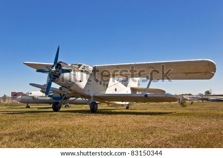 old russian airplane on grass and blue sky background - stock photo