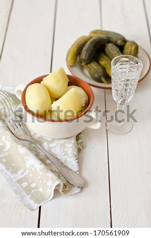 Old Russian dish of boiled potatoes, pickles and a glass of vodka on an old white table - stock photo