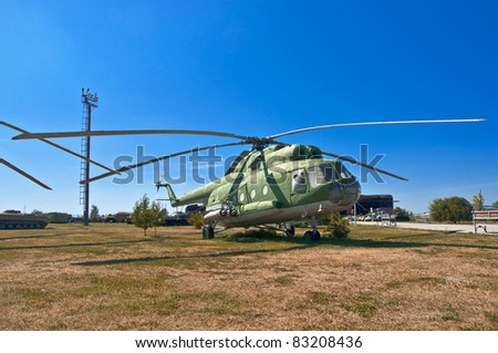 old Russian helicopter on the grass. Against the background of blue sky. - stock photo