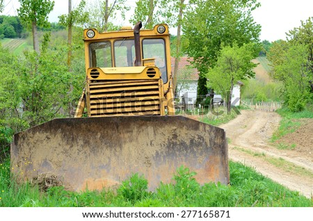 Old Russian-made crawler parking on the grass (front view) - stock photo