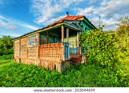 Old russian rural house with ivy at porch - stock photo