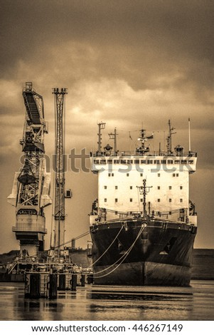 Old Russian ship in port with floating cargo cranes alongside. Vintage effect and noise added. - stock photo