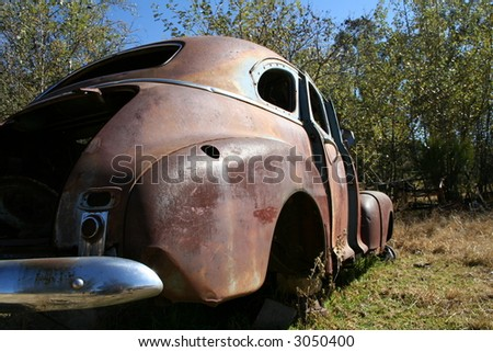 Old rusted car wreck from behind - stock photo