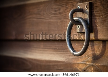 Old rusted chain link attached to the wooden wall of a barn on a farm - stock photo