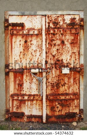 Old rusted doors chained and padlocked shut - stock photo