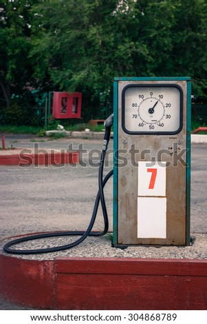 old rusted gas station with clock scale - stock photo