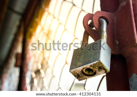 Old rusted gate is lock with a chain. - stock photo