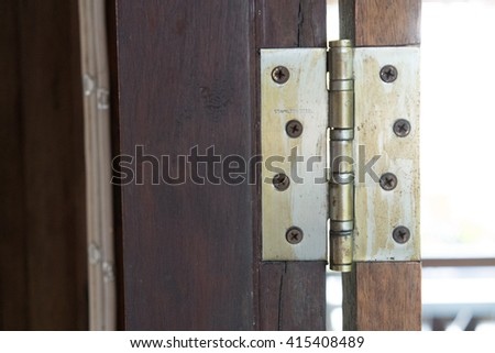 Old rusted hinge holding wooden door - stock photo