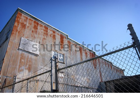 old rusted industrial building behind fence - stock photo