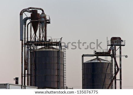 Old, rusted industrial style storage bins surrounded by crisp white sky. - stock photo